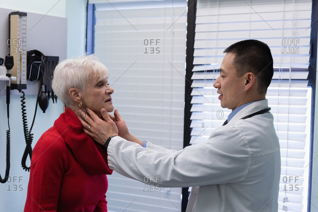 Side view of young Asian male doctor interacting with senior patient in the clinic