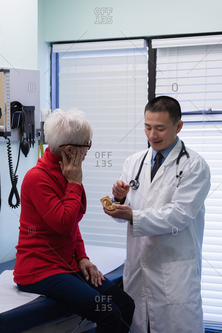 Front view of young Asian male doctor and senior patient discussing over ear model at clinic