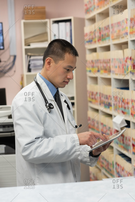 Side view of young asian male doctor holding digital tablet in the clinic