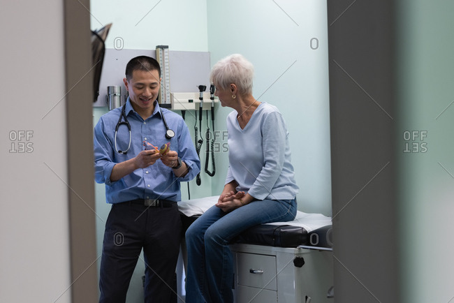 Young Asian male doctor and senior patient discussing over ear model at clinic