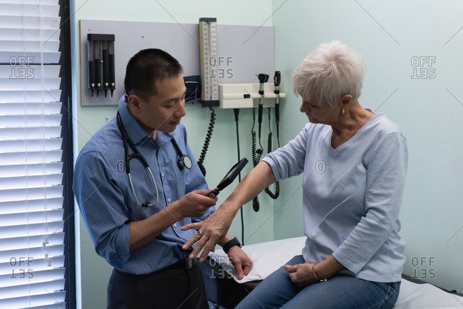 Front view of young Asian male doctor examining a senior patient with magnifying glass in the clinic
