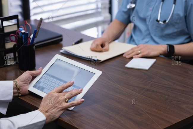 Mid section of senior woman holding digital tablet in clinic