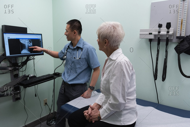 Side view of young Asian male doctor discussing over x-ray report on computer at clinic