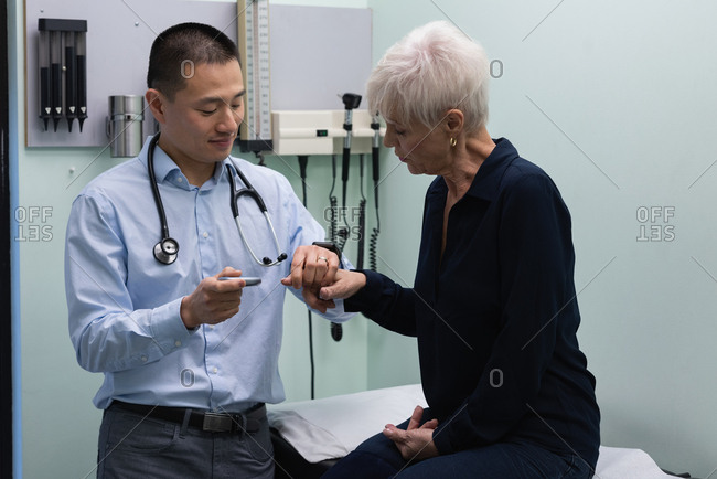 Young Asian male doctor measuring blood sugar level with glucometer of senior woman in the clinic