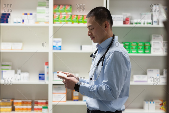 Side view of young asian male doctor holding medicine and standing in clinic