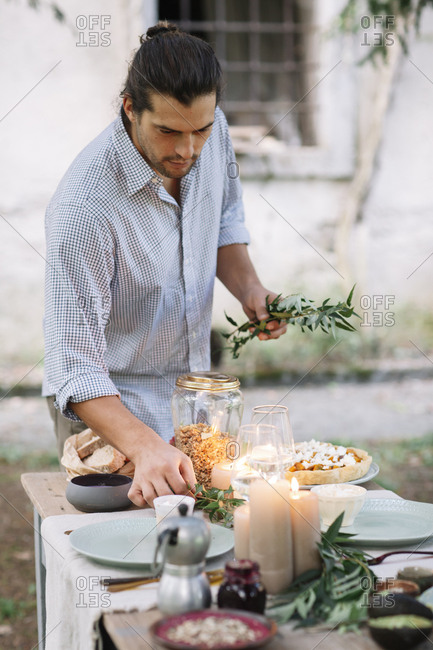 Man preparing a romantic candelight meal outdoors
