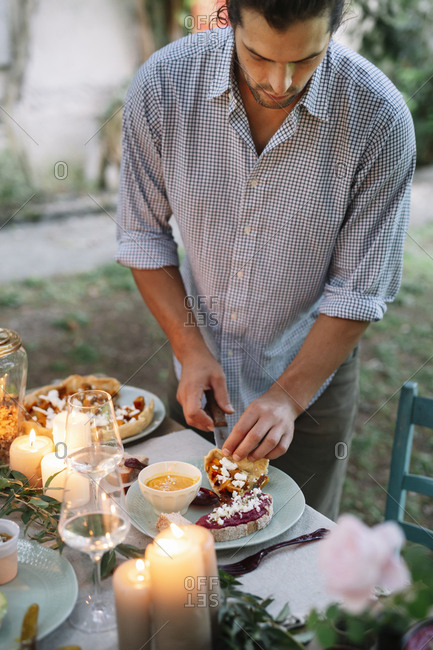 Man arranging a romantic candelight meal outdoors