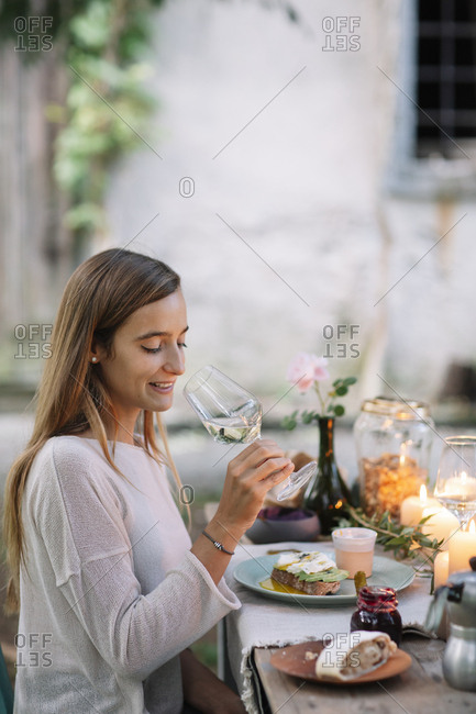 Woman tasting glass of wine at garden table
