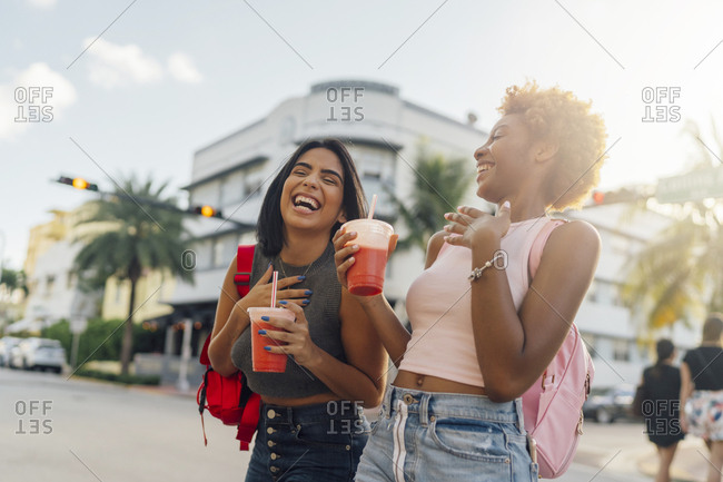 USA- Florida- Miami Beach- two happy female friends having a soft drink in the city