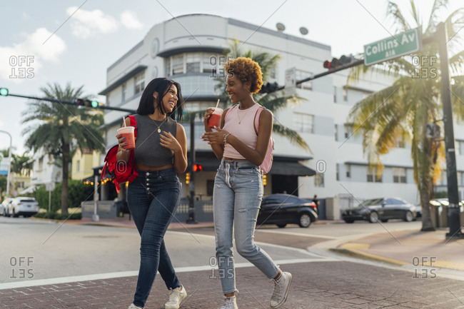 USA- Florida- Miami Beach- two happy female friends having a soft drink crossing the street