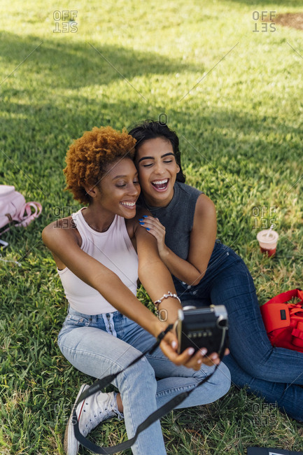 Two happy female friends taking an instant photo in a park