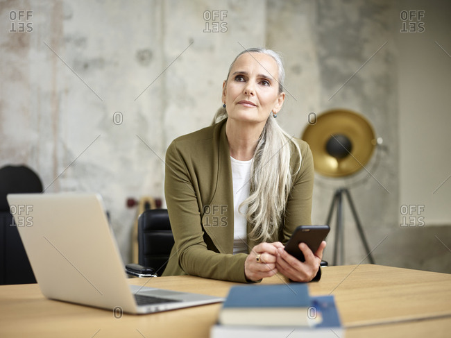 Businesswoman with cell phone in office looking up