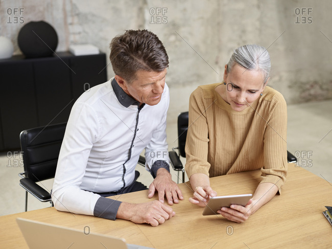Businessman and businesswoman sharing tablet in office