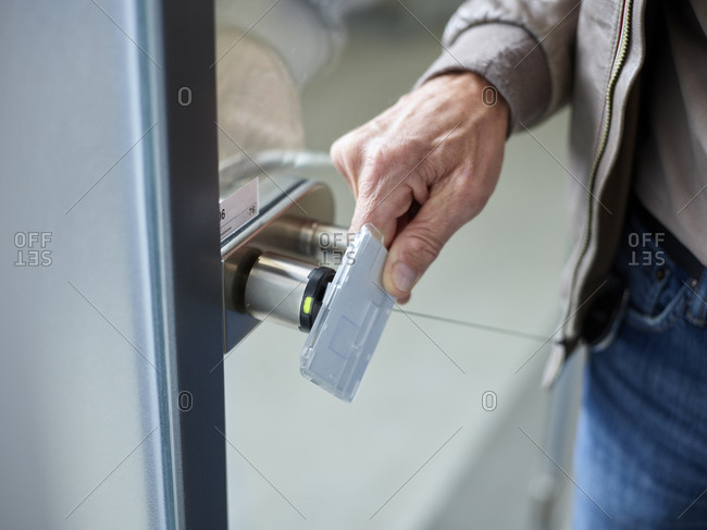 Close-up of businessman in office opening door with access card