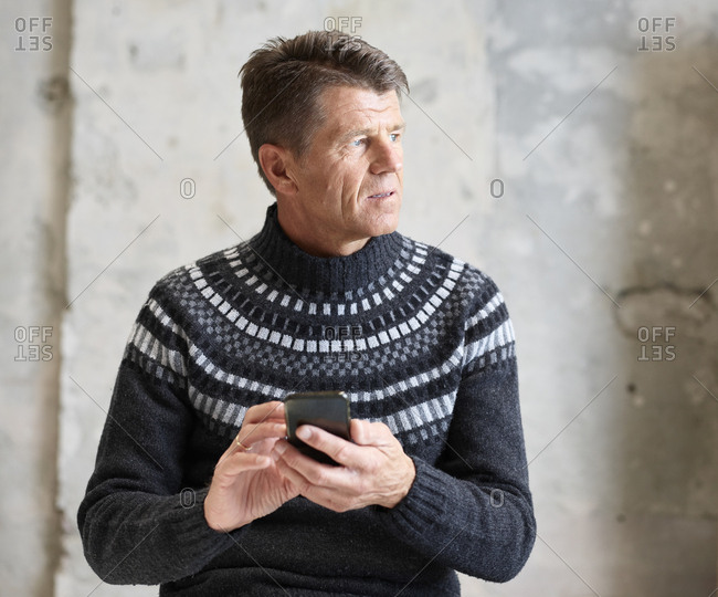 Man wearing pullover holding cell phone