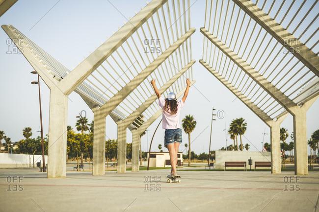 Girl on skateboard- raising arms- rear view