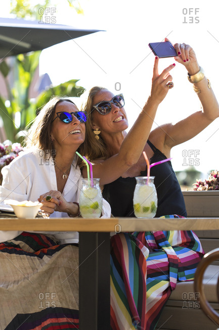 Happy girlfriends sitting outdoors with cocktail glasses taking a selfie