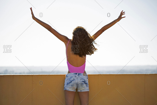 Portrait of teenage girl- raising arms- rear view