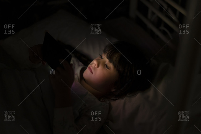 Girl lying in bed using smartphone at night