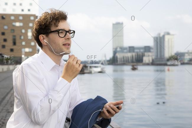 Germany- Berlin- businessman using smartphone and earphones outdoors