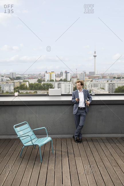 Germany- Berlin- businessman relaxing on roof terrace with a drink