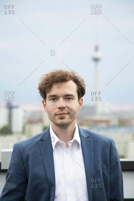 Germany- Berlin- portrait of  businessman with stubble and  curly brown hair on roof terrace