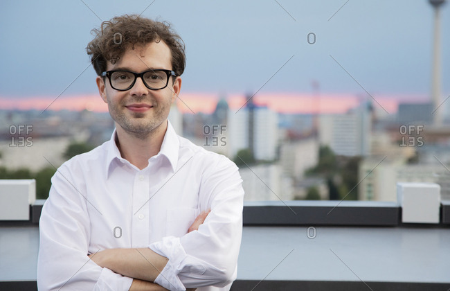 Germany- Berlin- portrait of successfull businessman on roof terrace by sunset