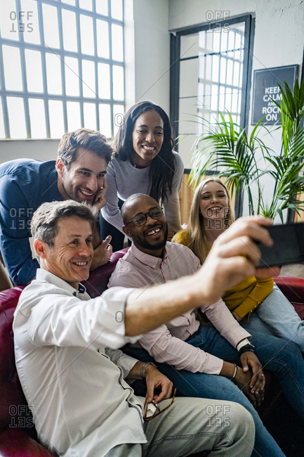 Happy business team taking a selfie in loft office