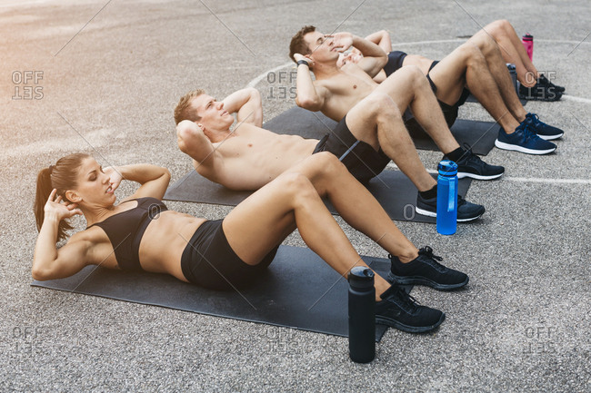 Sporty team of two women and two men- situps