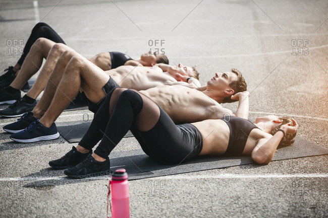 Sportive team during situps - Offset