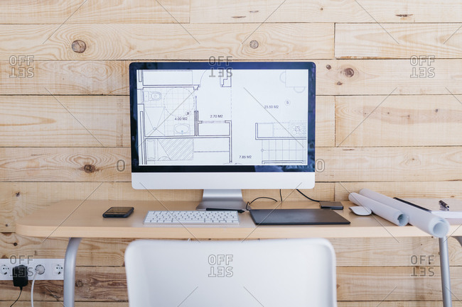 Desk in a home office with floor plan on the computer