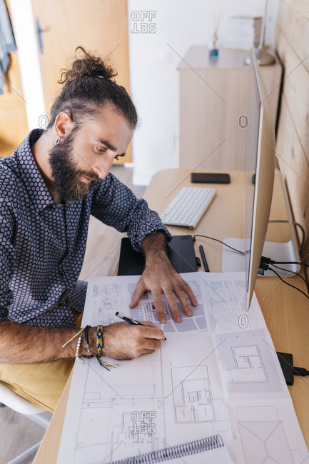 Young architect working at home with blueprints