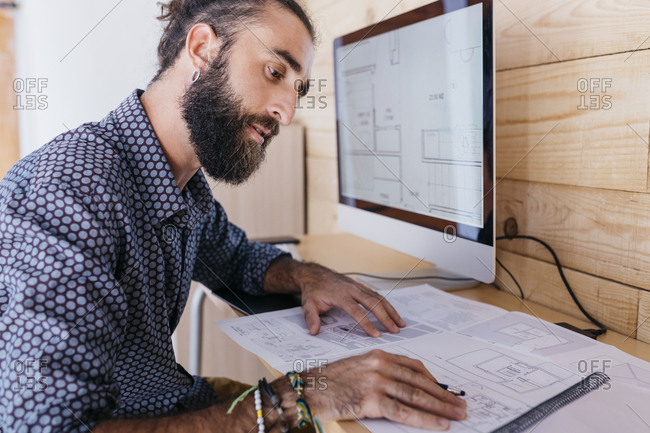 Young architect working at home with blueprints and computer