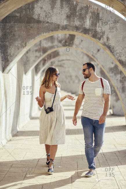 Spain- Andalusia- Malaga- tourist couple walking under an archway in the city
