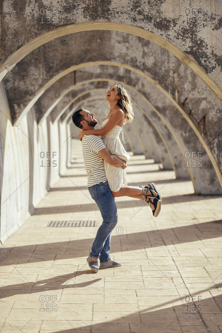 Spain- Andalusia- Malaga- happy man lifting up girlfriend under an archway in the city