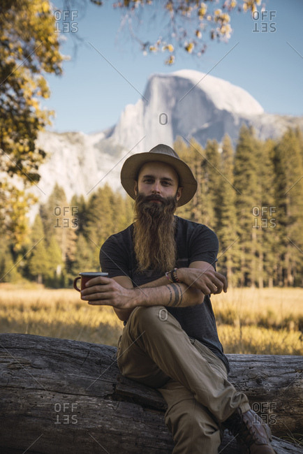 USA- California- portrait of bearded man sitting on a log in Yosemite National Park