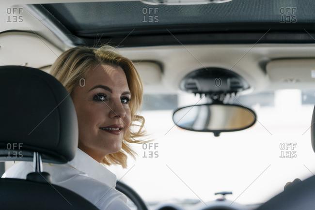 Smiling businesswoman in car turning round