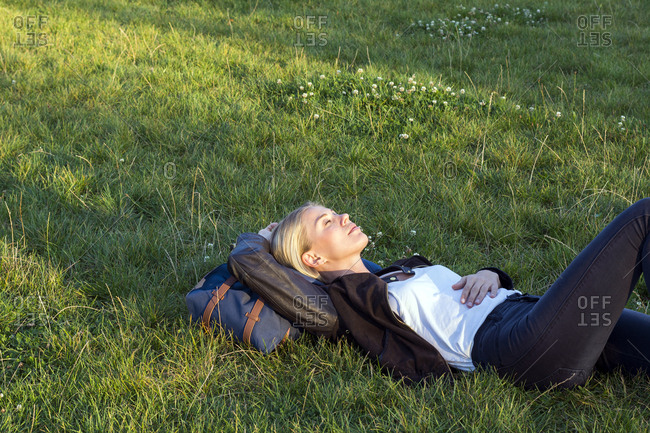Woman lying on a meadow in a park relaxing