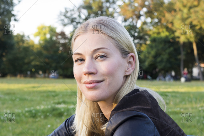 Portrait of content blond woman relaxing in a park