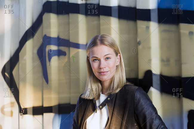 Portrait of blond woman in front of container
