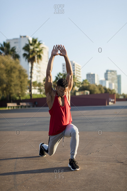 Fit man warming up before workout- doing lunges