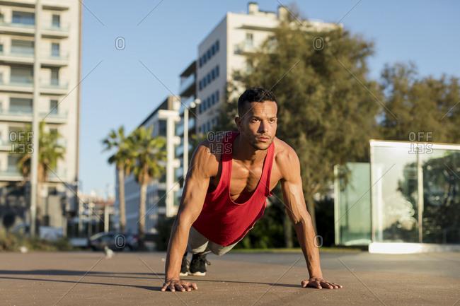 Muscular man doing pushups in the city