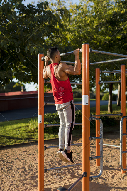 Fit man working out in climbing parcour- doing pull ups