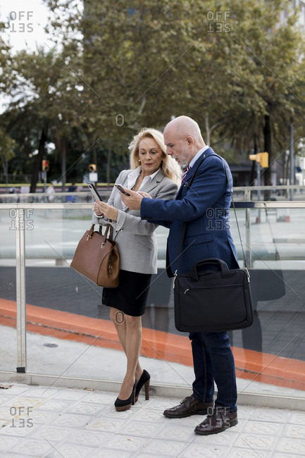 Senior businessman and businesswoman using cell phones in the city