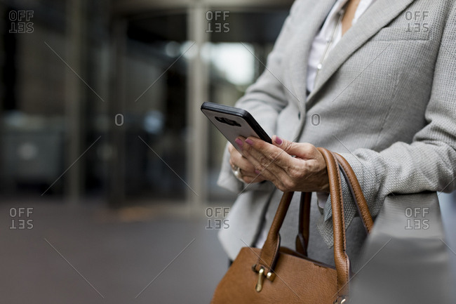 Close-up of businesswoman with cell phone and handbag