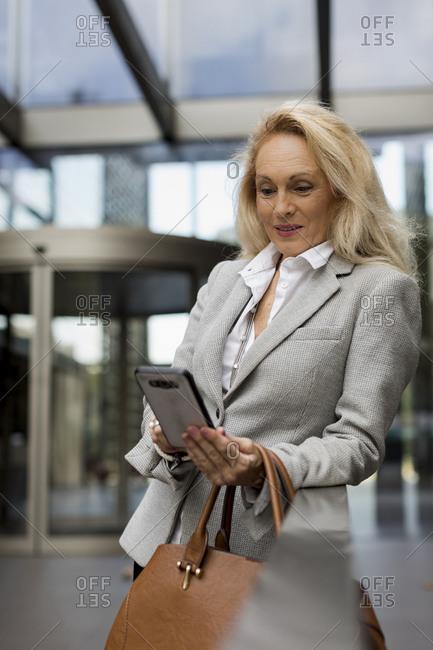 Senior businesswoman using cell phone in foyer
