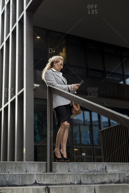 Senior businesswoman checking cell phone outside office building