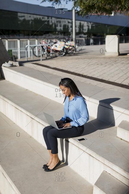 Businesswoman using laptop- sitting on stair