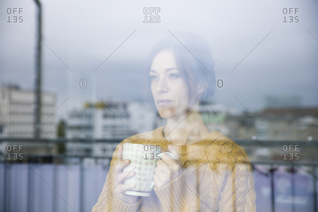 Sad woman standing at the window- drinking tea