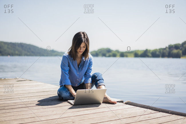 Mature woman working at a lake- using laptop on a jetty